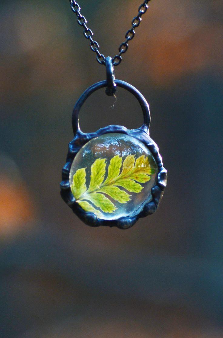 Little fern leaf encased in glass pendant.