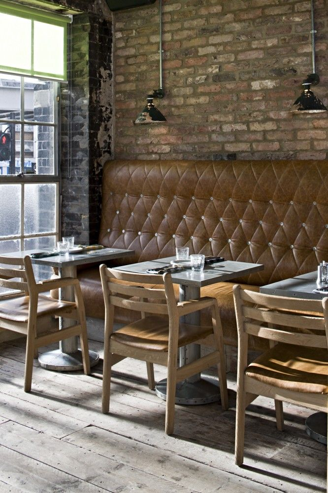 I like the rough-finished vibe here: rough-sawn hardwood flooring, brick walls and (faux?) leather banquette.