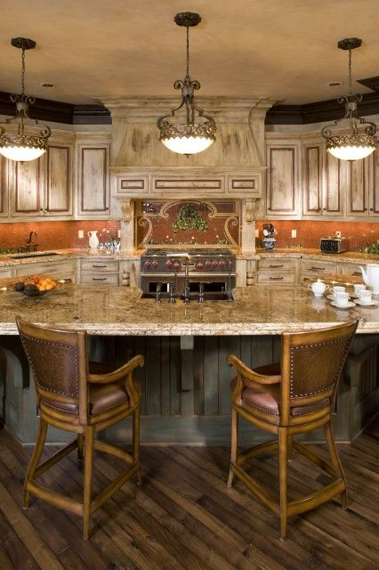 Lovely kitchen done in soft earth tones, with distressed cabinets  (via John Kraemer & Sons)