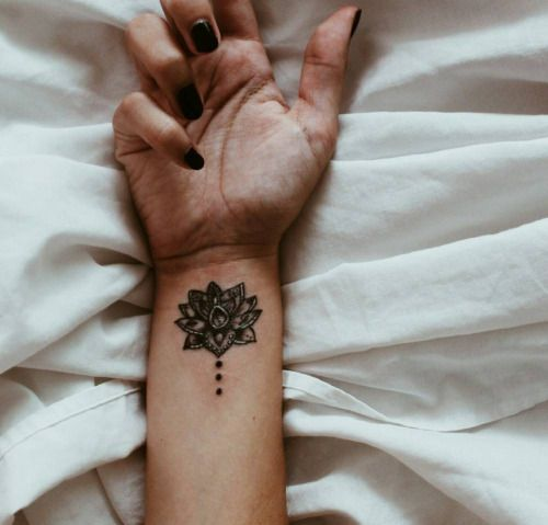 Lotus tattoo on the right inner wrist.                              …