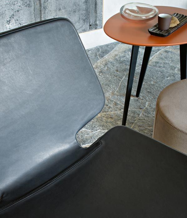 LEMA   The neat design style with hints to the art world of Roberto Lazzeroni characterises this lounge chair. Elegant re-interpretation in modern key of the dreamy look of the furniture in the 50s, WERNER has a black metal frame, thin, yet strong, in contrast with the extensive forms. Lacquered wood petals resting on metal structures that confer a lightweight look and a touch of 50s design to FLOWERS tables, in line with Roberto Lazzeroni' style.