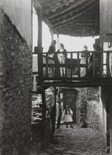 Women stand on a covered balcony, and a man stands in a lower doorway. 1900s. Location: Andritsaina, Greece. Photographer: FRED BOISSONNAS/National Geographic Creative