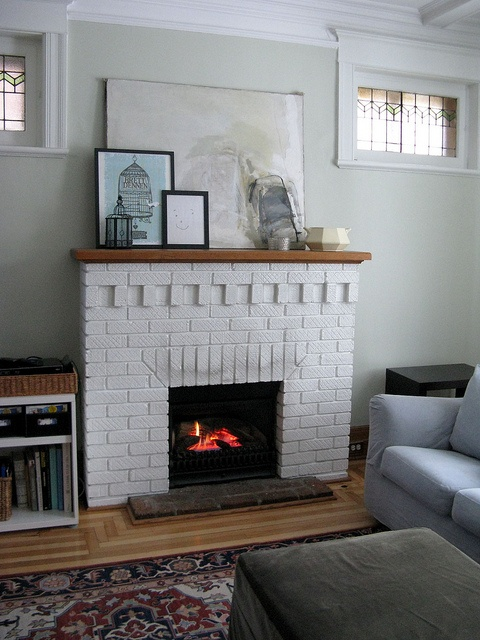 white brick fireplace. imagining a white floor to ceiling built-in bookcase surrounding it.