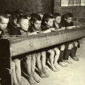 Greece, 1942-1944. Students at an elementary school; a galloping inflation imposed by the German authorities paying for goods on the Greek market with counterfeit money, made new shoes an unaffordable luxury, especially for growing children.