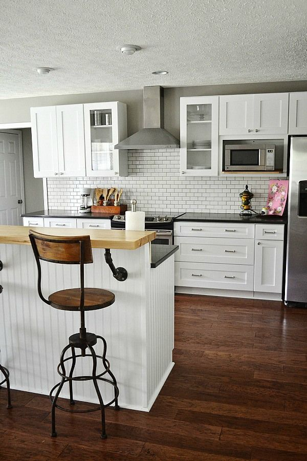 Subway tile backsplash, industrial barstool in a white kitchen