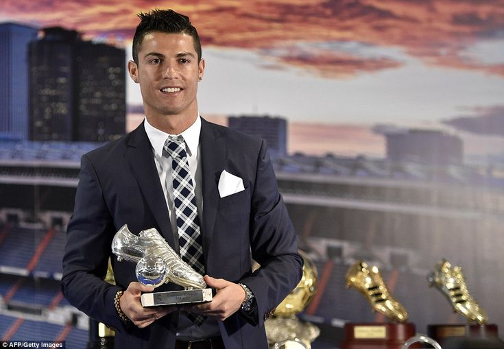 Cristiano Ronaldo poses with a trophy recognising his achievement of becoming Real Madrid's all-time leading goalscorer.