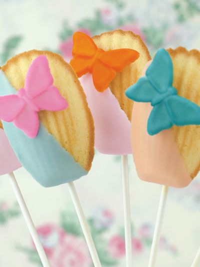 Butterfly Madeleine Pops - Butterfly Madeleine Pops 1. Prepare scratch or commercially-prepared madeleine cookies. 2. Dip edges of madeleines into melted and tinted white chocolate ganache and allow to set up. Chill if necessary. TIP: It is best to use oil-based colors to tint chocolate-based products. 3. Remelt ganache and dip one end of a candy stick in it; insert this dipped end into the bulk of the cookie. Allow to set up. 4. Attach decorations with a bit of ganache or icing to finish.