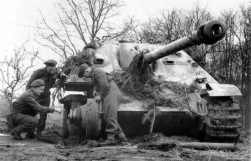 """Canadian soldiers inspect an SAU German """"Jagdpanther"""" tank, disabled with artillery fire from the 6th Regiment of the Royal Canadian Army near Klever Reichswald. It was the location of the Battle of the Reichswald, North Rhine-Westphalia in Germany between the Rivers Rhine and Maas at the Dutch/German border (Operation Veritable), in February and March, 1945."""