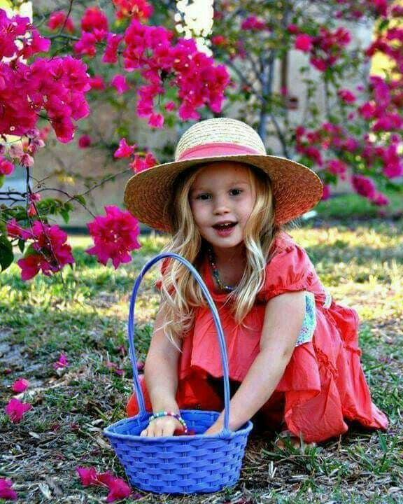 Little girl collecting flowers in a basket.
