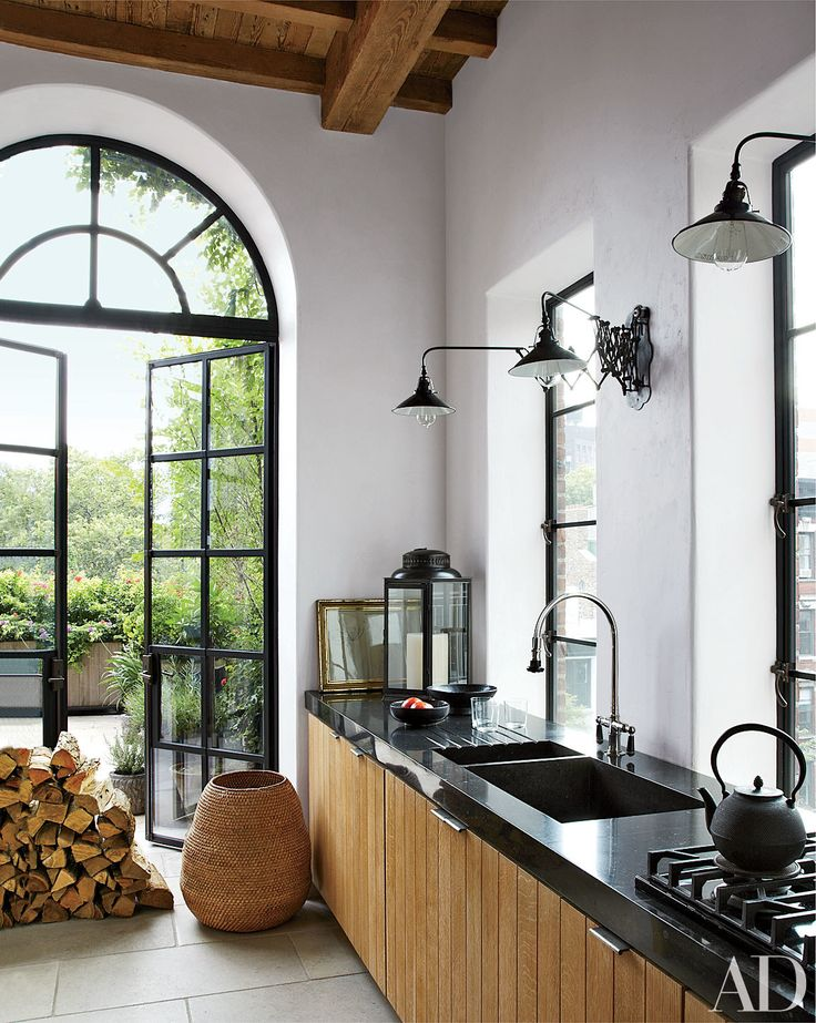 In this Manhattan house decorated by Alfredo Paredes, industrial light fixtures and bluestone countertops complement white-oak cabinetry in the kitchen. See more black kitchen countertop inspiration now.