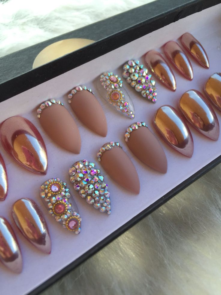 Rose gold chrome press on nails with matte and genuine Swarovski Crystal accent nails. Available in any shape & size.  Choose a 10 Nail set or a Full Set of 20 nails (All Sizes) if unsure of sizing. Sizes: XS, S, M, L  XS: THUMB 3, POINT 6, MIDDLE 5, RING 7, PINKY 9  S: THUMB 2, POINT 5, MIDDLE 4, RING 6, PINKY 9  M: THUMB 1, POINT 5, MIDDLE 4, RING 6, PINKY 8  L: THUMB 0, POINT 4, MIDDLE 3, RING 5, PINKY 7  FULL SET: You receive 20 nails size 0-9. With your order you will also receive a…