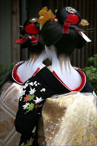"""Japan. Because of the rainy weather, these two new maiko in Miyagawa-cho, Kyoto, had to wear plastic covers over their priceless silk brocade obi on the day of their misedashi (their first day as maiko, when they are presented and introduced to the district with their new professional names). Sanbonashi is the """"three-legged"""" prong of bare skin left unpainted at the nape of the neck only on very special occasions. 