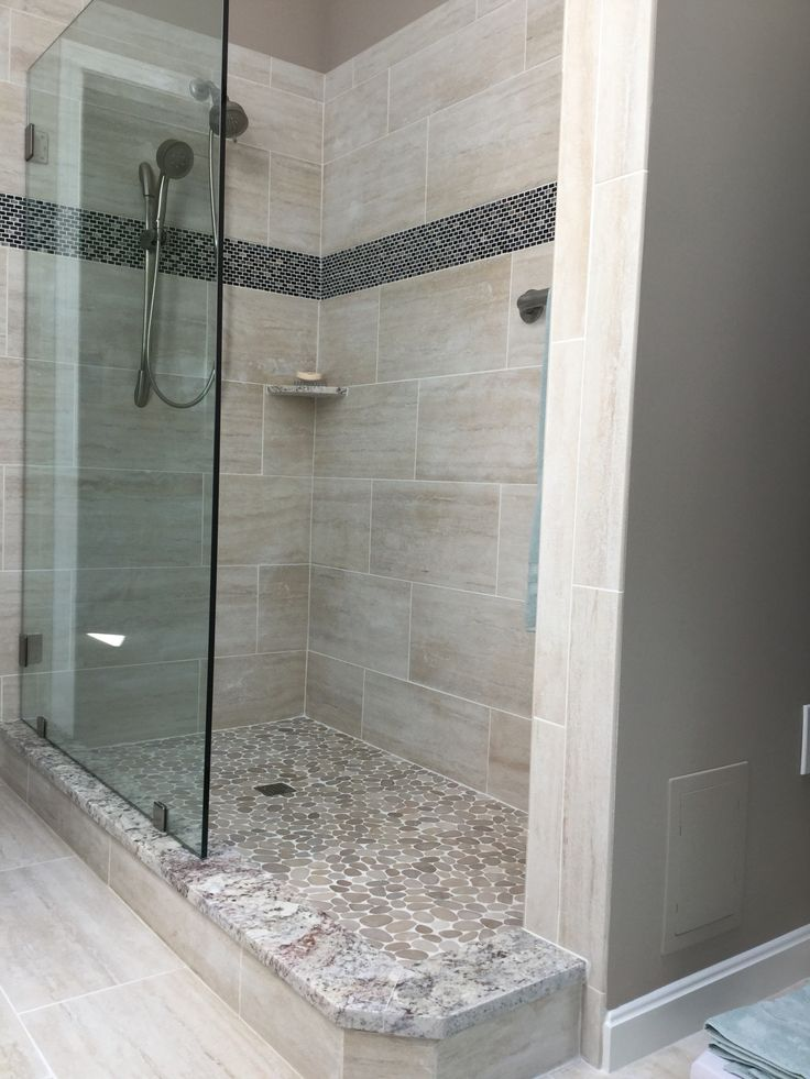 Walk in shower features pebble flooring with flattopped