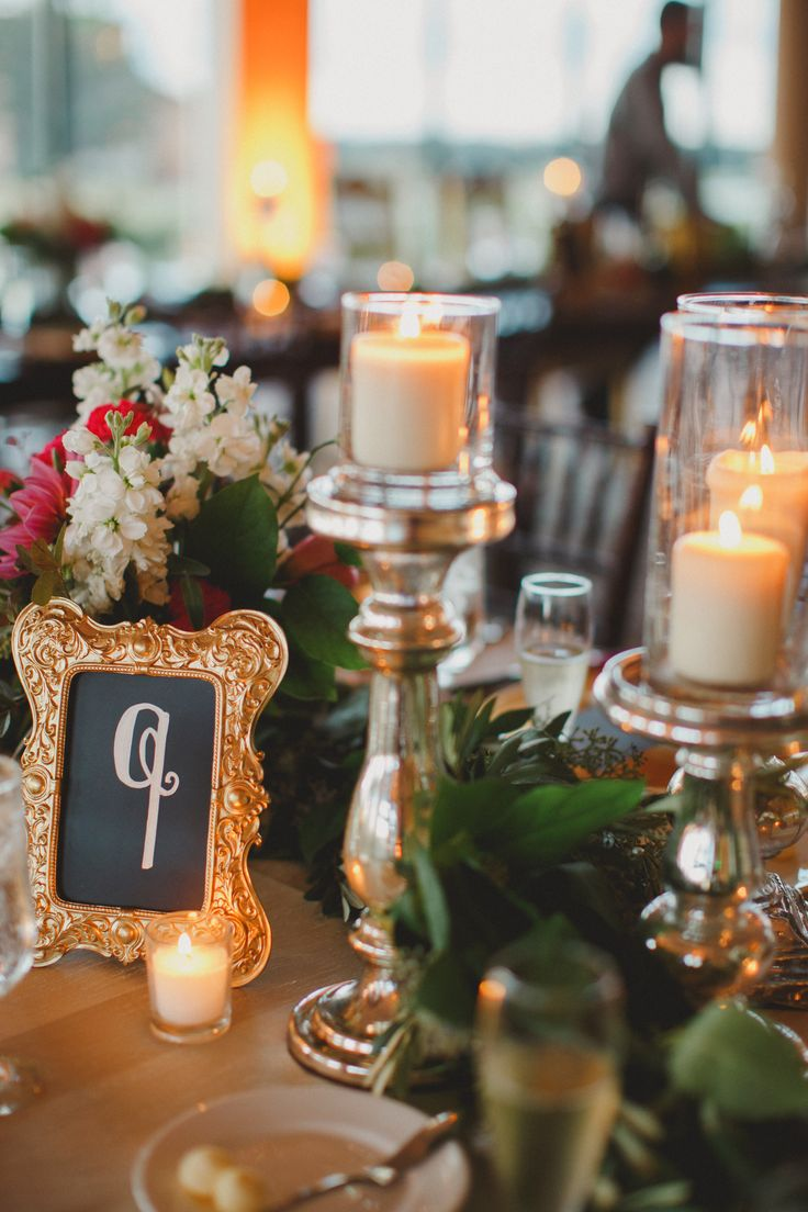 a trio of ivory pillar candles on mercury glass pedestals added a glow to the reception tables.