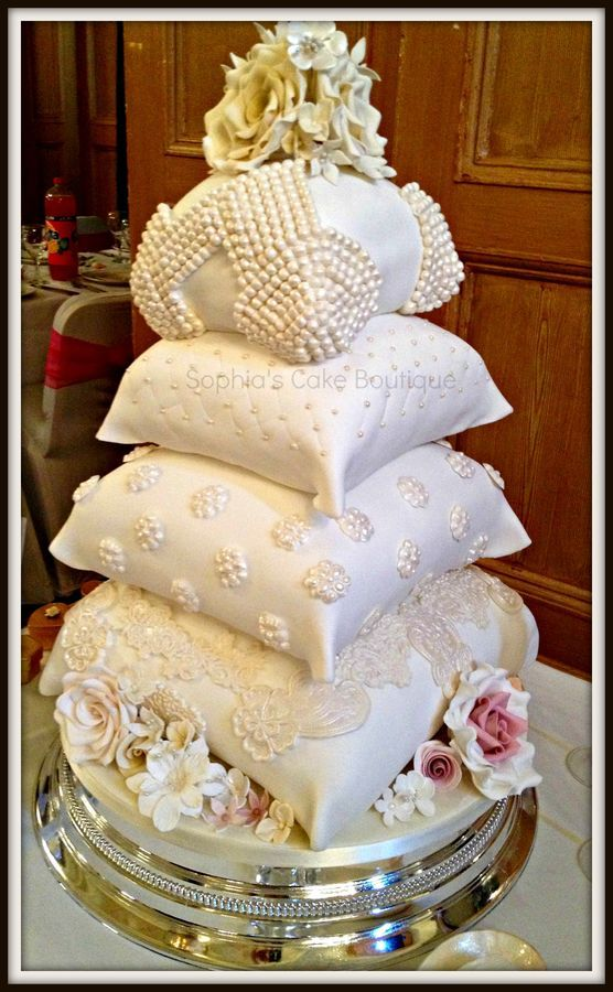 ivory pillow cake in alternating vanilla and lemon flavours. Cake adorned with flowers, pearls and lace.