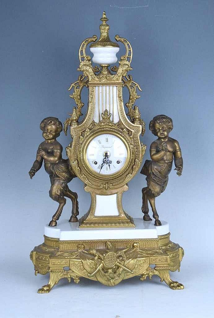 20th Century Bronze lyre form clock with white enamel center and base, clocked flanked by cherubs...