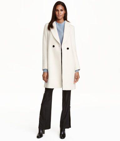 Naturweiß. Taillierter Kurzmantel aus weichem Wollmischgewebe. Der Mantel hat zwei kontrastfarbige Knöpfe, Seitentaschen und einen Gehschlitz im Rücken. Gef