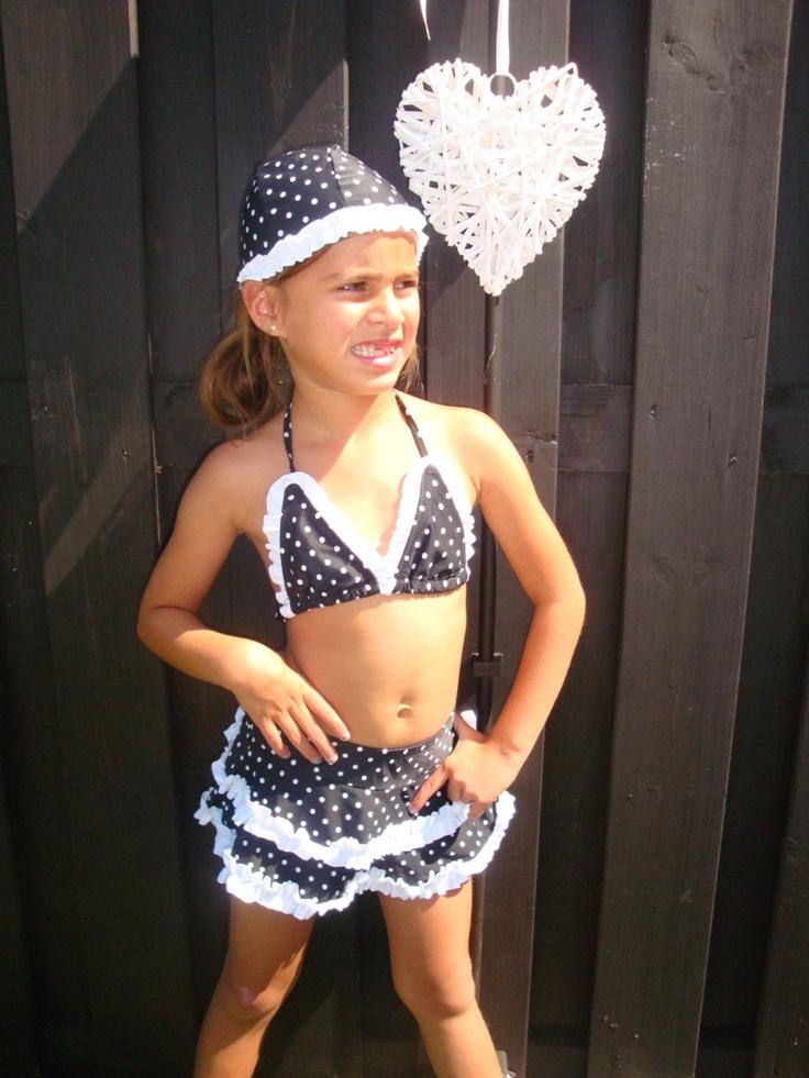 Een bikini in zwart met witte polkadots. Het rokje zit vast aan het broekje. Bijna alle badkleding bij Dottig heeft bijpassende badmutsen! Mooi gekleed gaan je kinderen de zomer tegemoet.