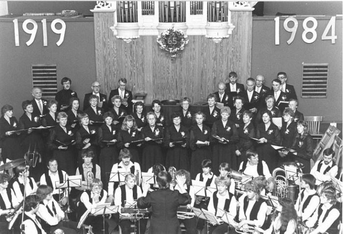 """Viering van het 65-jarige bestaan van de Christelijk gemengde zangvereniging """"God is mijn lied"""" te Reitsum. Dit vond plaats in een volle Geref.kerk te Reitsum. Op de foto het koor met op de voorgrond de chr.muziekvereniging """"Concordia"""" uit Wanswerd o.l.v. A. Travaille.   Plaats: Reitsum, ,    Datering: 2 november 1984"""