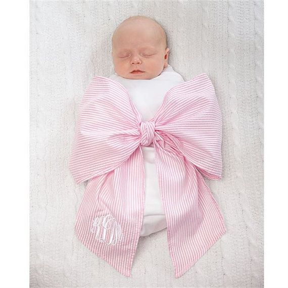 The Seersucker Swaddle Baby Blanket by is a lightweight batiste blanket perfect for swaddling your little one. The large seersucker fabric sash is attached to the blanket and ties in a nice big bow around your baby. A large 3-letter monogram looks great on the tail of the bow. These are perfect for newborn photos! The blanket has a triangular shape: 42 x 39 x 39 Size: Newborn Material: Main fabric - 100% cotton, Contrast fabric - 65% polyester, 35% cotton…