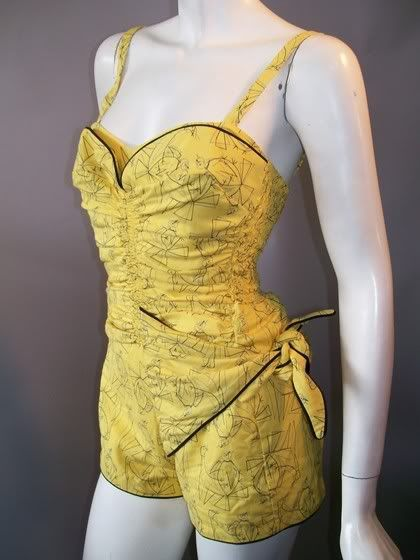 1950s bathing suit, sarong-inspired side wrap, boy shorts, ruched bodice with petal bust and smocked sides. Metal zip up back, by Catalina.