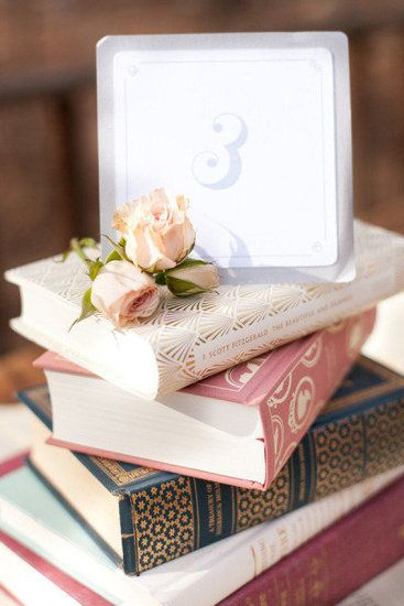 Page by Number: Stack pretty books as easy centerpieces with the table numbers on top.  Photo by Caroline Frost Photography via Style Me Pretty