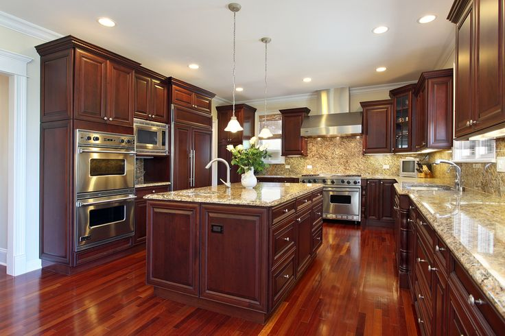 Large dark wood kitchen in luxury home. Kitchen opens up into living space and includes large central island with sink.  Floor is wood and c...