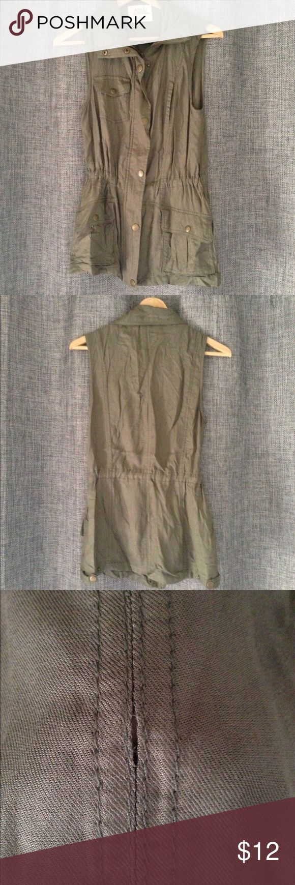 Khaki Green Anorak Style Vest Anorak style vest with waist-cinching drawstring. Zipper and button closure. Flap pockets along the front. *Small area on back seam has come undone and fabric is fraying along the side of one pocket. Jackets & Coats Vests