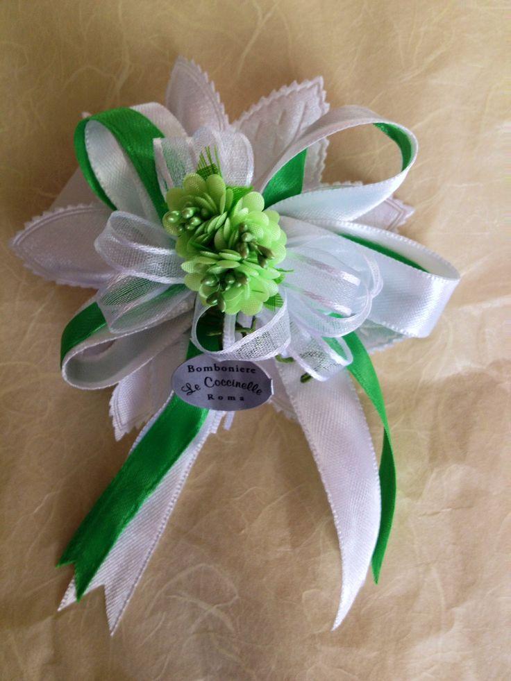Sacchetto a forma di petalo colore bianco, 5 confetti, 2 nastri raso colore bianco e verde, nastro bianco organza a coccarda, 3 fiori verdi. Bustina raso bianco, 5 confetti, 2 nastri raso colore bianco e verde, nastro bianco organza a coccarda, 3 fiori verdi, coroncina argento.