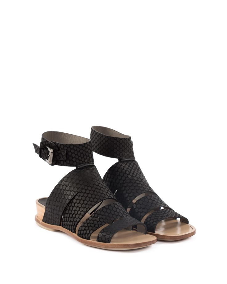 Leather bands flat sandal, ankle buckle fastening. Small wood platform and leather sole