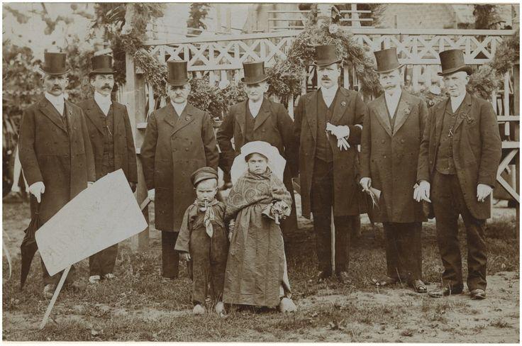 Aalst, Een groep uit een optocht van 28 nummers [waaronder 8 praalwagens] bij de inhuldiging van de nieuwe burgemeester G.van Dommelen: 'een Noordbrabantsche boer en boerinnetje met een groene paraplu' [de jongen is 2 jaar]. Tekst op bord: 'Hulde aan den Burgemeester' 1916