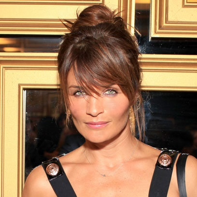 With the addition of a side swept fringe, Helena Christensen gives wispy hair a sleeker look. The loose strands of straight hair give the sophisticated updo a relaxed feel.