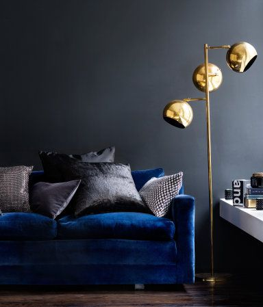Deep blue velvet sofa, dark grey walls, gold coloured spherical floor lamp                                                                                                                                                                                 More