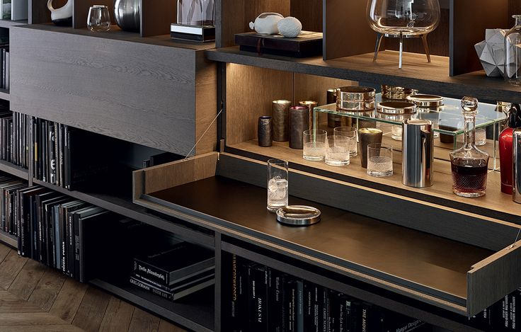Detail of Jet jutting out flap door in cenere oak, with insert in transparent glass used as bar and mirror back panel, top in black hide.