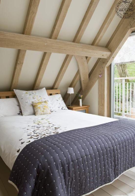 Bedroom in roof of oak frame house in Cornwall, by Roderick James Architects