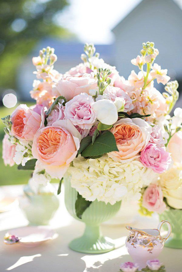 pink and white wedding centerpiece in mint vase with peonies, hydrangea, and garden roses on vintage table