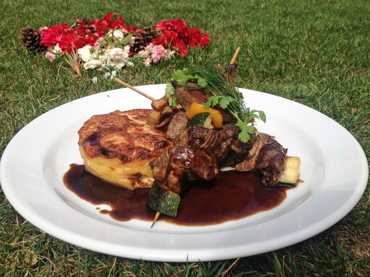 Grilled beef sirloin skewers served with potatoes au gratin,  vegetables and…