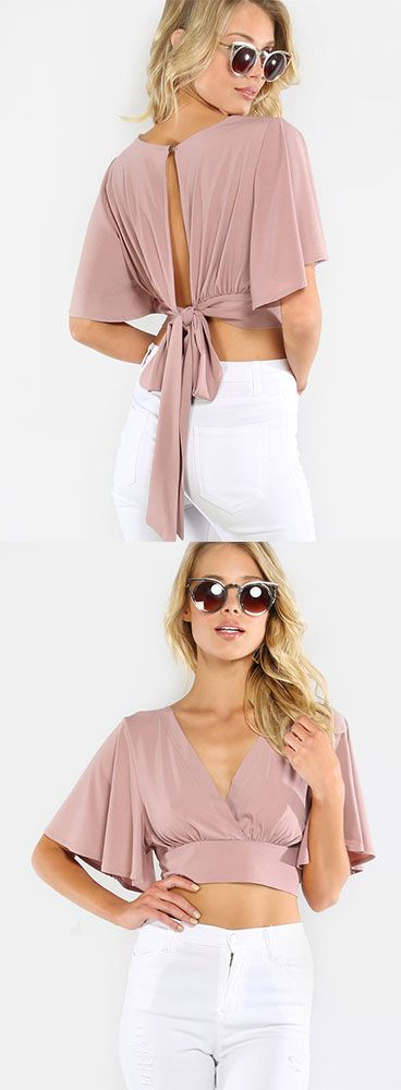 """Add a feminine piece to your ensemble with the Flowy Crop Wrap Top! Features a a v-neck, pleated front, wrap closure and fluttery short sleeves. Top measures 10.75"""" from shoulder to bottom hem. Wear with high waist denim for a retro inspired ensemble. Modeled in a size S."""