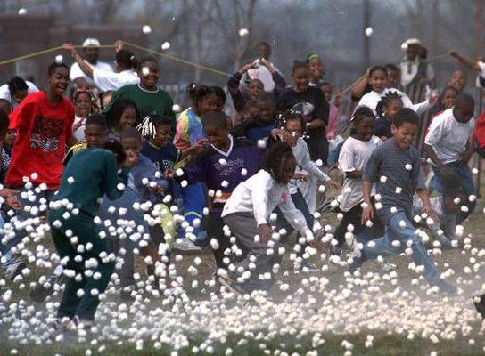 """Marshmallow Drops   In this event, Easter sweets literally rain from the sky. In a tradition that dates back several decades in southern Michigan, tens of thousands of marshmallows are dumped onto children from helicopters. The tradition has since spread to other areas. Above: Children rush to grab marshmallows at the sixth annual """"Great Marshmallow Drop"""" at Belle Isle in Detroit Saturday, April 3, 1999."""