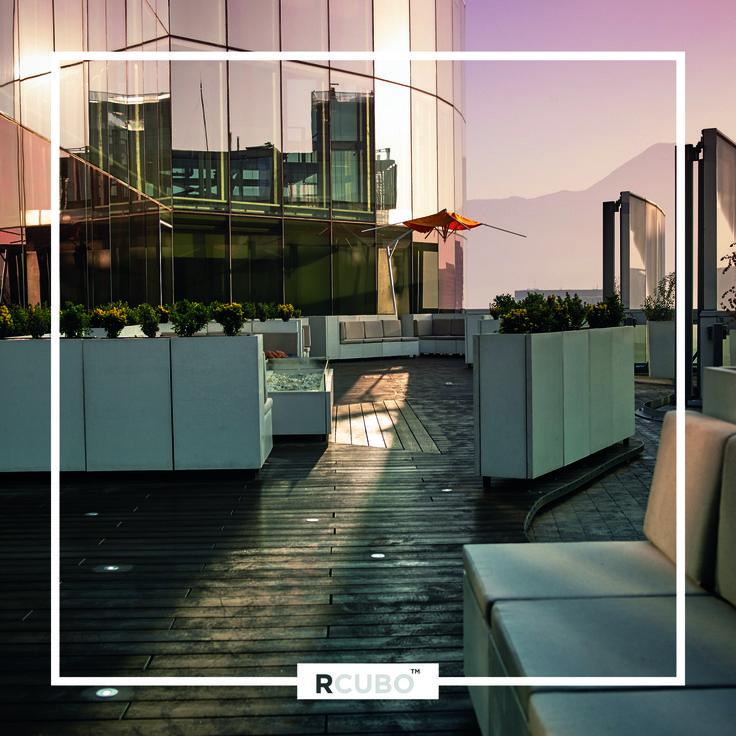 Conjunto modular de terraza exterior en cemento granítico RCUBO color Marfil, incluyendo jardineras, bancas y mesas de centro con quemador de etanol