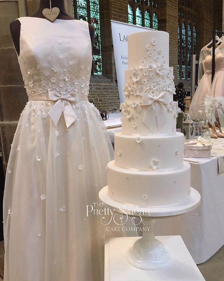 Wedding cake inspired by the Charlotte Balbier 'Hepburn' wedding dress. Delicate blush with pretty bow, appliqué blossoms and sequins detail