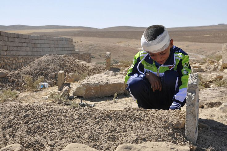 LOST FATHER: Mohammed Moses grieved by the grave of his father, who was killed by a suicide car bomb attack, in Qabak, Iraq, Monday. Deadly ...