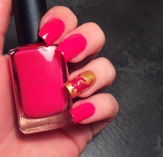 Nail art rossa e un dito oro con su una decorazione floreale perfetta per gemelli come segno zodiacale