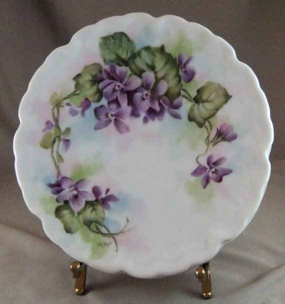 """Hand painted violets with bright green leaves adorn this porcelain plate. The violets were painted several times with great attention to detail and fired in a kiln after each painting until the desired depth of color was achieved. It measures 6-1/2"""" in diameter."""