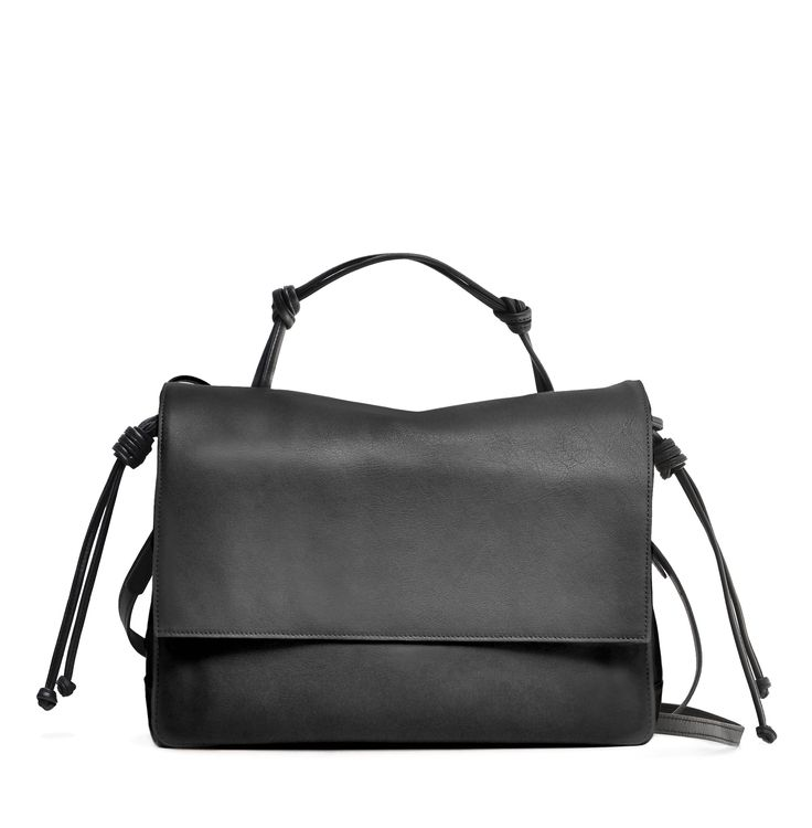 The Handheld in Black from von Holzhausen featuring natural grained soft Italian leather with painted edges. Comes with removable crossbody strap, two open pockets on interior and removable signature wallet.