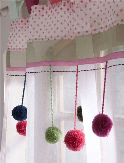 Detalle de cabecera de cortina aportando color a la tela de visillo blanco inferior. Pompones de lana muy divertidos.
