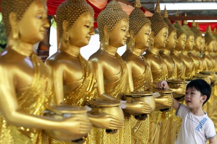 May 5 _ A guy puts some coins into golden statues of Buddha during the Wesak Day, which celebrates Buddha's birthday and the day that he reached spiritual enlightenment. The Buddhist temple of Thai Chetawan in Petaling Jaya, near Kuala Lumpur | Malaysia