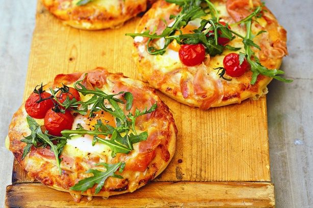 Egg and Bacon Pizzas  4 individual pizza bases  4 tbs (1/3 cup) sundried tomato pesto  125g grated mozzarella  4 small eggs  12 cherry tomatoes (we used truss)  Olive oil and balsamic vinegar (optional), to drizzle  Baby rocket leaves, to serve