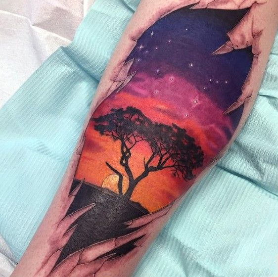 Gorgeous colored lonely tree with sunset tattoo on leg
