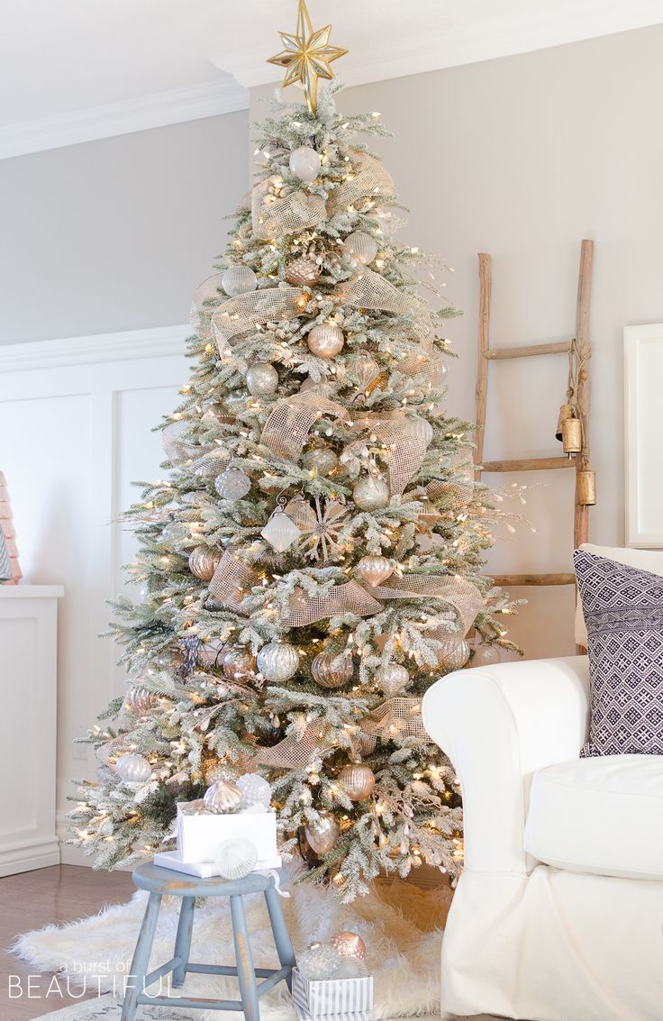 A snowy flocked Christmas tree decorated in silver and rose gold adds a big dose of holiday cheer to this modern farmhouse living room